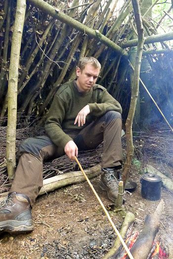 Intermediate bushcraft student, knife, cooking pot and hand-drill in shelter