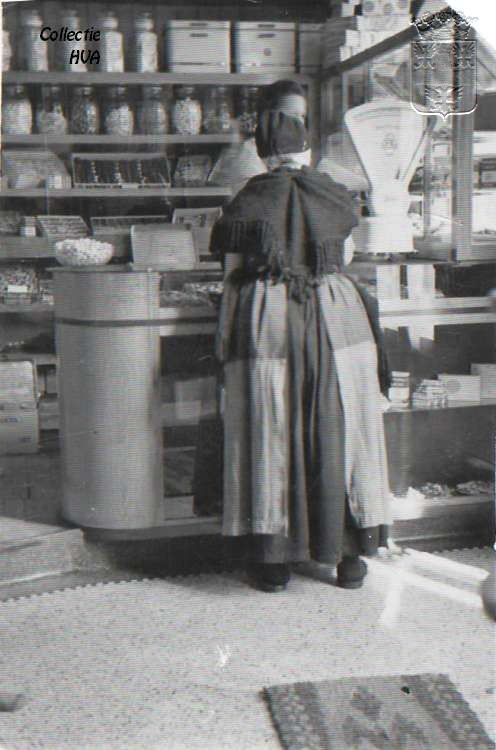 note: apron covers most of back,wearing mules,  De winkel van bakker Joosse.