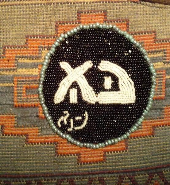 Mary's beaded patch featuring CARET lettering sewn onto her purse.