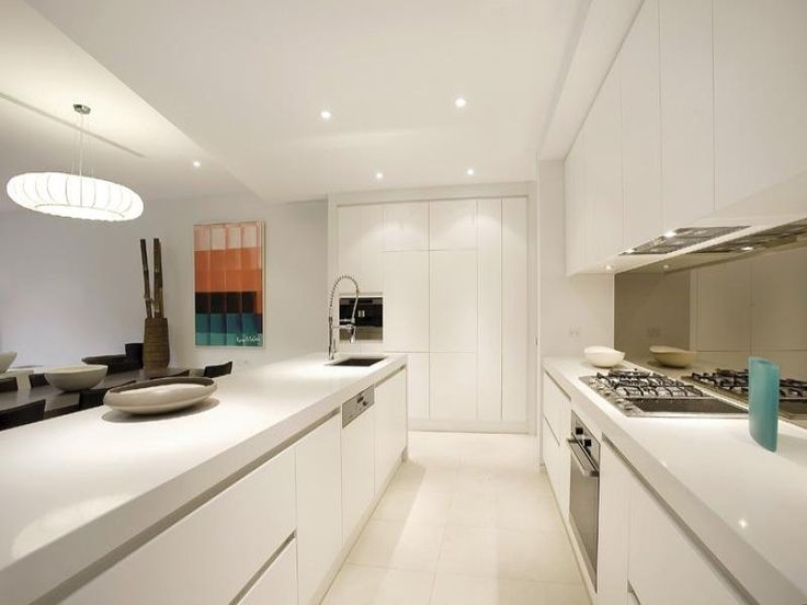 White kitchen with thick bench tops and handle free cupboards