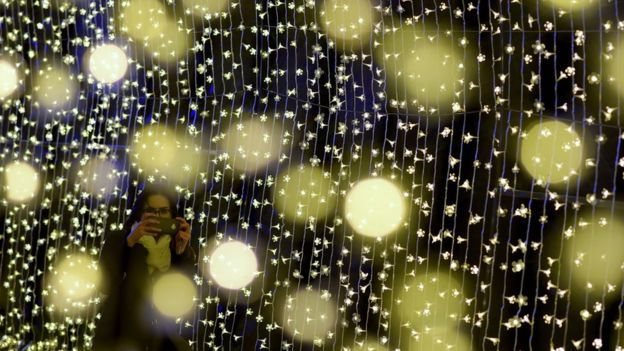 A visitor takes a picture of a light installation in Canberra,