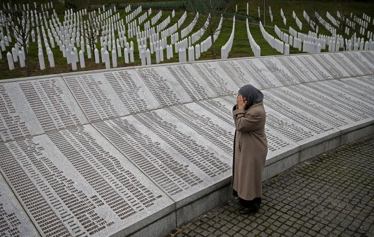 BOSNIA AND HERZEGOVINA: Bida Smajlovic, who lost her family in the Srebrenica massacre, prays near the memorial plaque before watching the Trial in Hague Tribunal.