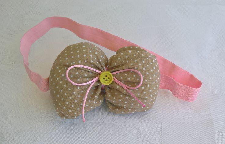 Κορδέλα μαλλιών με μπεζ πουά γεμισμένο φιόγκο και ροζ λάστιχο.