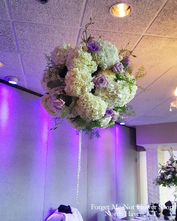 Ball of white hydrangea and lavender roses with crystals hanging above a table for a centerpiece at a wedding reception. By Forget Me Not Flower Shop, North Haven, CT