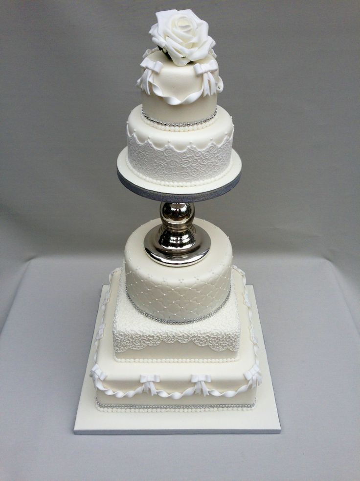 A Dazzling 5 Tier Cake Separated With Silver Glass Feature