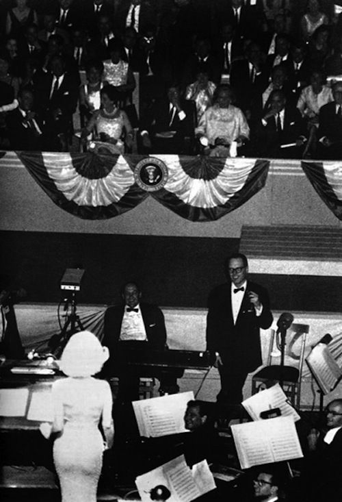 """NYC. Manhattan. May 19, 1962: Marilyn Monroe sings """"Happy Birthday Mr. President"""" and """"Thanks for the Memory"""" at the JFK Birthday Gala at Madison Square Garden. // Marilyn (foreground) is standing with her back to us, in front of JFK  (in the dark background between two ladies)."""
