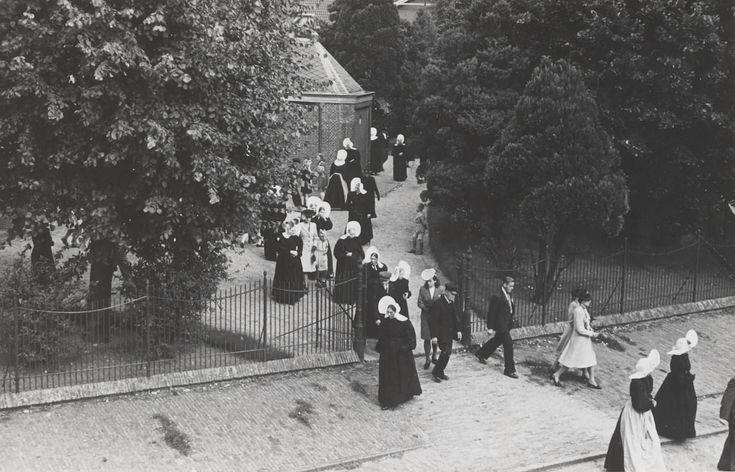Kerkgang te Huizen. De kerk gaat uit. Mannen en vrouwen, gekleed in zowel streekdracht als modekleding, verlaten de kerk. 1945 #NoordHolland #Huizen #isabee #oorijzermuts #cornet