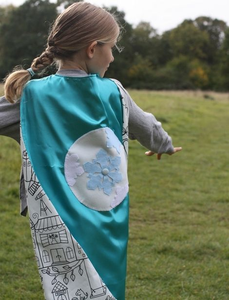 This beautiful cape was inspired by winter and the popular film Frozen.)  I have lined the cape with a play themed black and white 100% cotton fabric depicting lots of different play scenarios. The motif is a snowflake design of ice blue and glittering white snowflakes, hand embroidered on with a shimmering,metallic thread. It fastens at the neck with a simple velcro closure. Dimensions - this one is 70 cms in length. I can make different lengths, dependent on age of child. Price - From £25