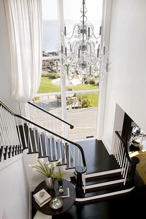 I love the dark wood stairs and the pure white everywhere else and of course the long drapes and Chandelier!