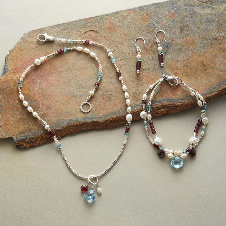 "The passionate glow of red garnet and the frosty cool of sterling silver, apatite and pearls join a glittering faceted blue topaz in handcrafted jewelry that makes the event. USA. Necklace 17""L, bracelet 7-1/2""L, earrings 1-3/8""L. $238."