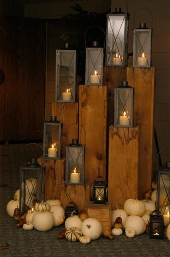 take 4x4 (or) 6x6 pine posts and stain. Then cut to various heights and place lanterns on top.