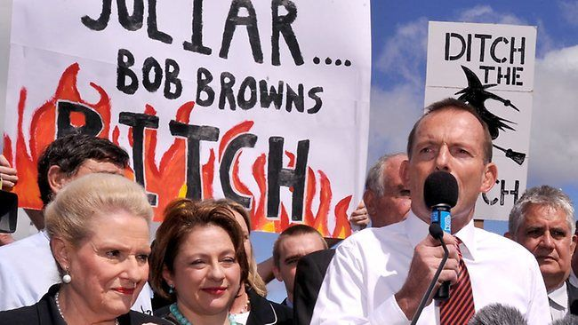 """Tony Abbott speaking at a rally in front of posters spelling """"Ditch the Witch"""". These posters were aimed at Julia Gillard his political opponent at the time. The fact that Abbott continued his speech even after he saw the posters being behind him demonstrates and reinforces already existing belief that he perpetuated and tolerated sexism and misogyny in his politics."""