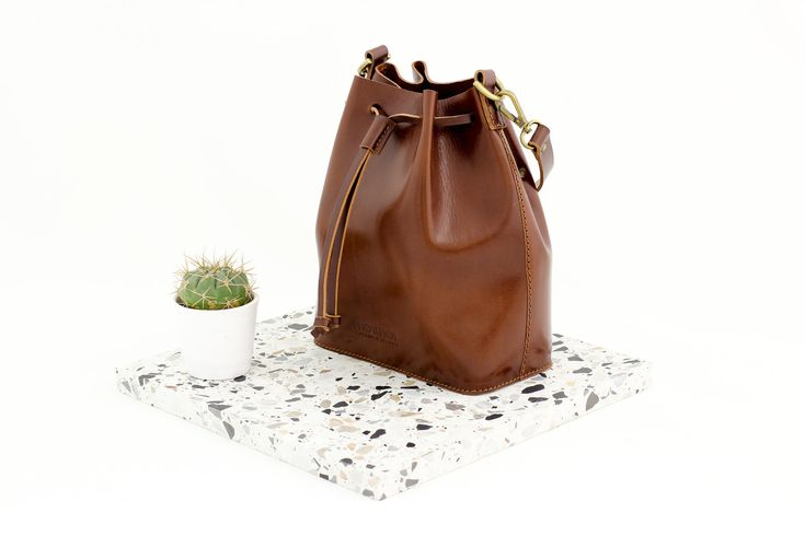 MARILIN small bucket bag in brown leather. A tad smaller, a tad cuter. Drawstrings fastening on top adds a cute touch. Handmade sustainably from vegetal tanned leather.