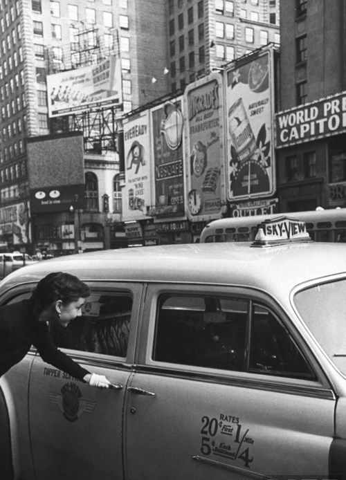 Audrey Hepburn getting into a taxi in Times Square. NYC 1951.