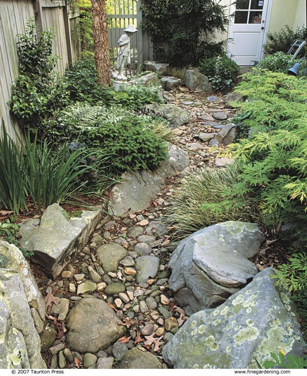 Building a natural stream to guide rain water around the house    After construction and planting, the streambed looks like a natural part of the landscape.