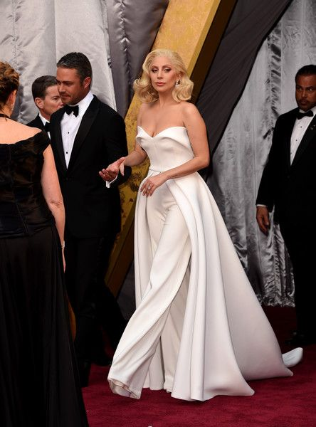 Lady Gaga and fiance Taylor Kinney walk together at the 88th Annual Academy Awards.