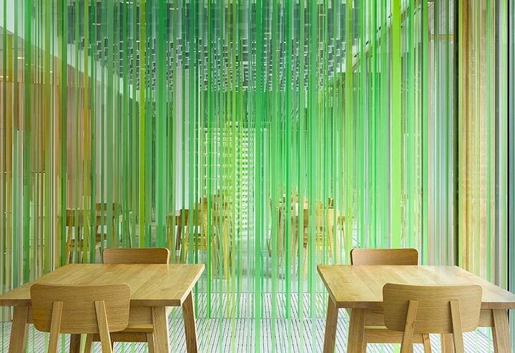 Semi-transparent strips in shades of green line wall panels inside Skunk & Relax coffee shop.