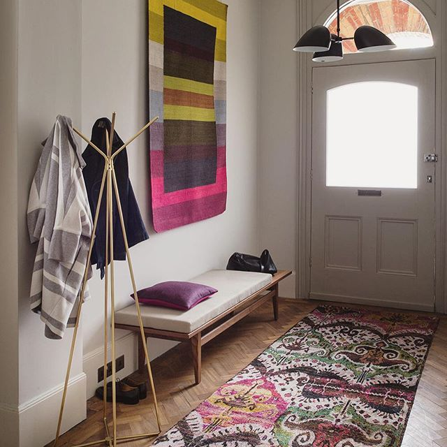 Punches of strong colour and pattern work well in an otherwise neutral hallway painted in the softest white grey. A flatweave rug in a bold geometric pattern is treated as wall art and a richly patterned floor runner as decoration to a wood floor. Tap for tags... --- #hallway #rug #interior #interiordesign Styling Claudia Bryant, photography Paul Raeside