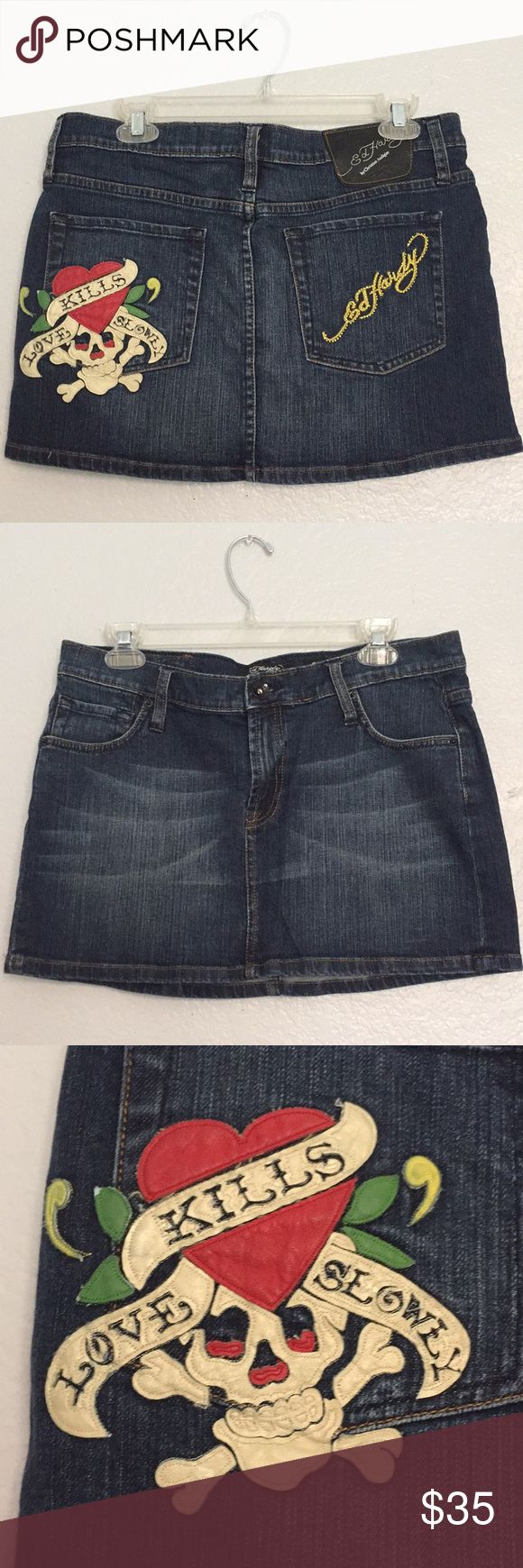 """Ed Hardy Jean Skirt Size 31. Ed Hardy Jean Skirt. Length 12"""" front 13 1/2"""" Back. Waist laying flat measures 17 3/4"""" across.Preowned and in excellent shape. Patch on pocket says Love Kills Slowly. Other pocket signature with jewels. Leather patch on waistband. Button and zipper fly closure. Please view all photos. 99% Cotton 1% Elastane Ed Hardy Skirts"""
