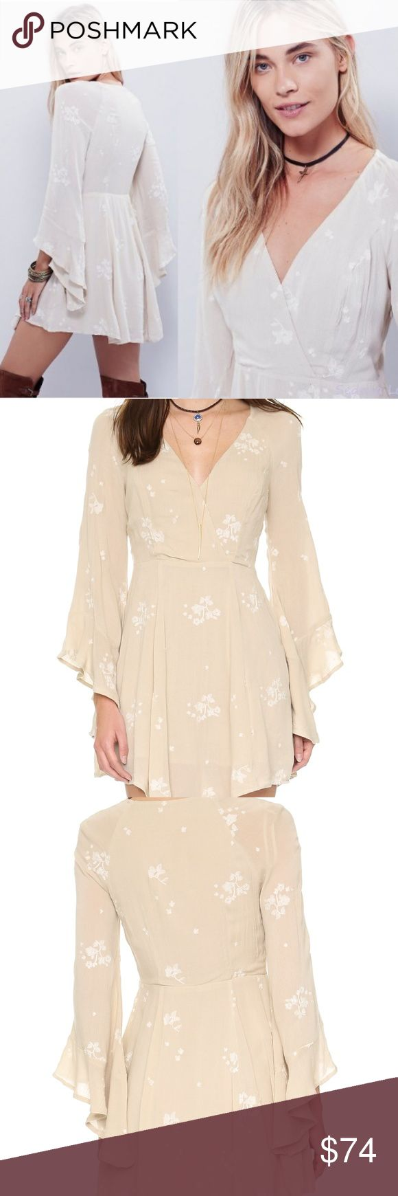 Free People Jasmine Embroidered Mini Dress Almond An airy Free People mini dress with a flared skirt. Ruffle cuffs and floral embroidery accentuate the romantic feel. Crossover V neckline. Long sleeves. Lined.  Fabric: Gauze. Shell: 100% rayon. Lining: 65% rayon/35% cotton. Hand wash or dry clean  Color Almond Free People Dresses Mini