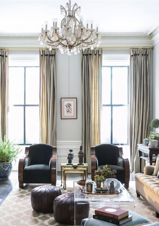 Gorgeous floor-to-ceiling drapes and glamorous crystal chandelier paired with a modern clear acrylic coffee table, mid-century arm chairs and bohemian Moroccan leather poufs.