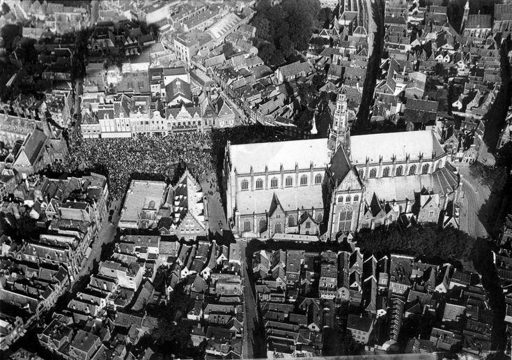 Gezicht op Haarlem vanuit de L.Z. 127 Graf Zeppelin tijdens de Hollandfahrt, 13 oktober 1929. Linksboven de schaduw van het ruim 200 meter lange luchtschip boven de ongeveer 100 meter lange Grote of St. Bavokerk. De Grote Markt ziet zwart van de mensen.