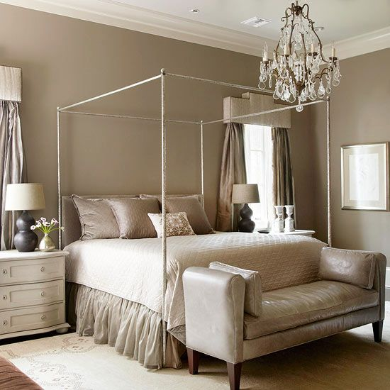 Embodied Elegance   A simple four-poster draws the eye up, up, and away in this dreamy bedroom. The shimmering chandelier in the center of the room also grabs attention and reflects light streaming in from the windows.  The room's tone-on-tone color scheme looks anything but dull thanks to a mixture of textures and subtle patterns. Accents of creamy white provide contrast and help the space feel more light and airy.