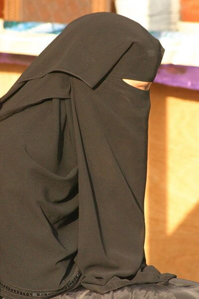 A Saudi woman wearing her hijab (veil) and abaya (body covering). According to Islamic law, women's clothing must not reveal anything about her body. Although the strictness and color of clothing varies from region to region, orthodox Muslims wear all black. Picture taken from Wikimedia Commons, a creative commons site, under the Attribution 2.0 generic license.