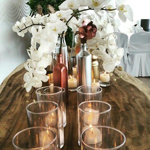Orchids, metallic bottles, candles