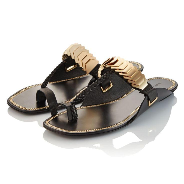 Werthaltig gefertigt, mit trapezförmigen goldfarbenen Metallapplikationen am Riemen, geflochtenem Steg aus schwarzem Leder und eingefasster Goldkette an der Decksohle.