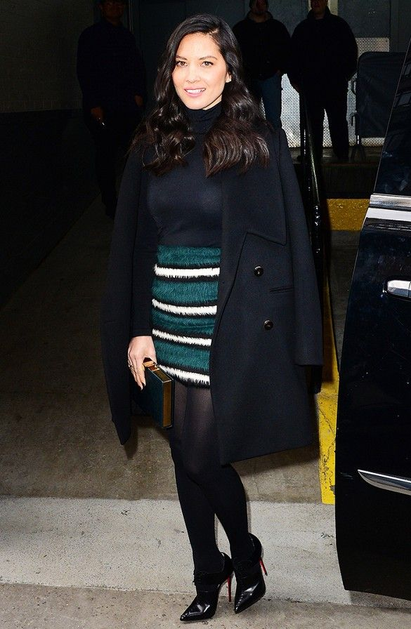 Olivia Munn in a sexy black turtleneck and striped mini skirt