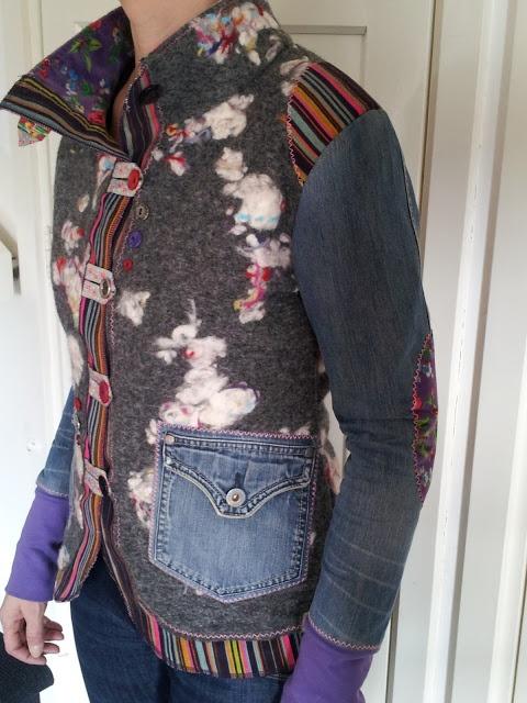 Jasje aanpassen, door verschillende stoffen en elementen te gebruiken zoals: - een zakje van spijkerstof; - lusjes en knopen; - gestreepte stof langs randen aan de onderkant en in de schouder; - tricot stof aan de onderkant van de mouwen.
