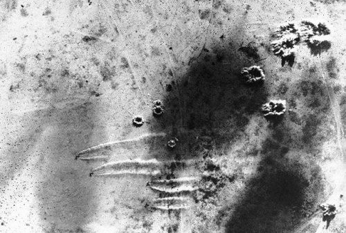Overhead view of a South African Air Force raid on the German airfield at Martuba, Libya, 6 July 1942. Note circular dust patterns of bomb bursts and lines of dust kicked up by scrambling aircraft. http://wrhstol.com/2DBTPem