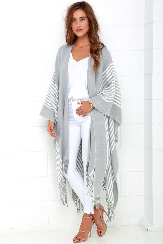 No other outerwear is as cool and sophisticated as the Swiss Alps Ivory and Grey Striped Poncho! Soft, medium-weight woven fabric with a handcrafted look and lovely light grey hue, shapes a draping open front that transitions into ivory striped patterning. A pointed hemline with decorative twisted fringe completes this dreamy Boho look.