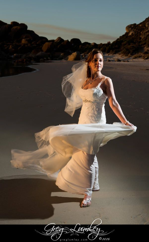 Bride twirling on a Cape Town beach in Cape Town at sunset by Greg Lumley