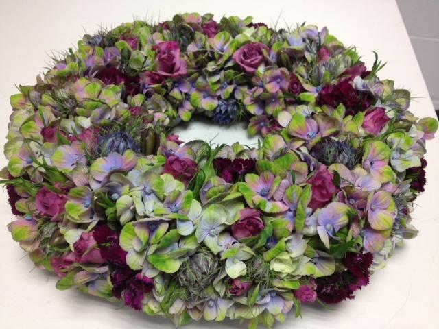 mensen houden van bloemen. Mooie krans van hortensia en o.a. trosroosjes.
