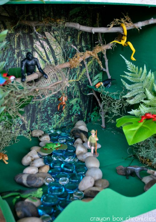 Rainforest Small World Sensory Bin built from a cardboard box by Crayon Box Chronicles