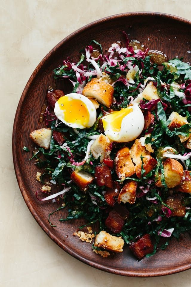 classic bistro salad — salade Lyonnaise — thin strands of kale and radicchio make up the base with bacon, eggs, and a surprising take on croutons topping it all off.
