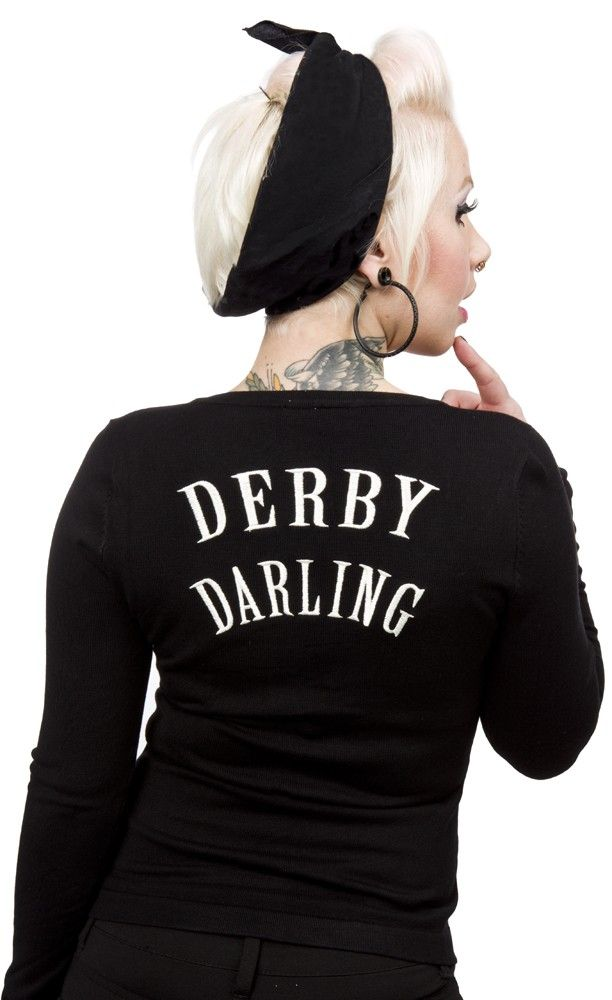 "SOURPUSS DERBY DARLIN CARDIGAN  Keep cozy warm when your not in the rink with the Derby Darlin' cardigan! This black cardigan features embroidered derby gal legs on the chest, red buttons & ""Derby Darling"" embroidery on back.  $50.00"