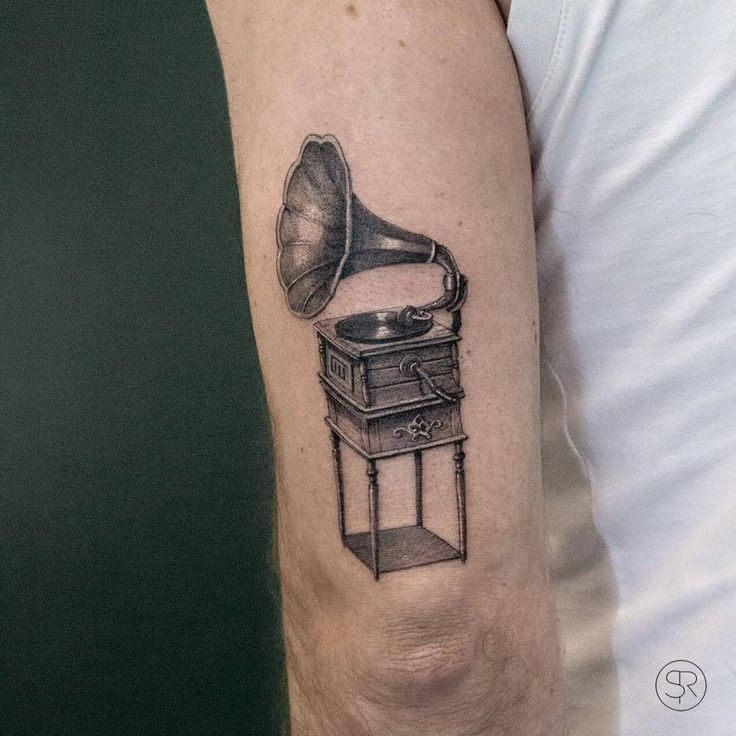 Fine line gramophone tattoo on the back of the left arm.