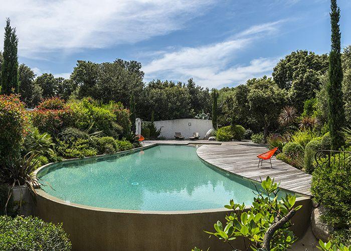La piscine se termine par un vaste mur de débordement arrondi, qui assure une surface de l'eau nette et haute sous les margelles.