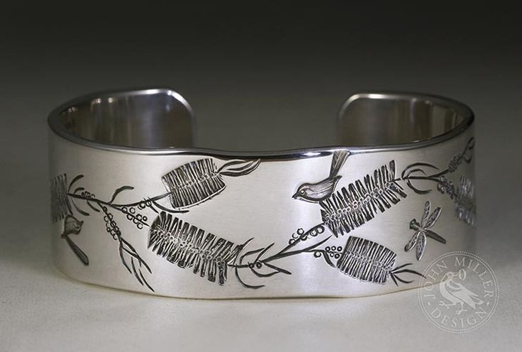 A stunning handcrafted sterling silver cuff featuring bottle brush flowers and blue wrens
