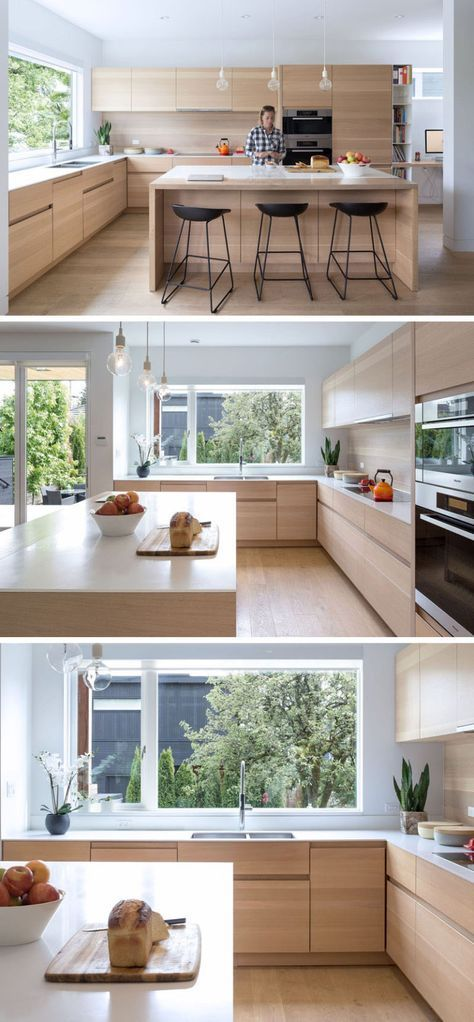 In this kitchen, a large window provides lots of natural light to the mostly wooden kitchen. Exposed shelves are used to store recipe books, and the kitchen has achieved a contemporary look by not including hardware on the cabinets.