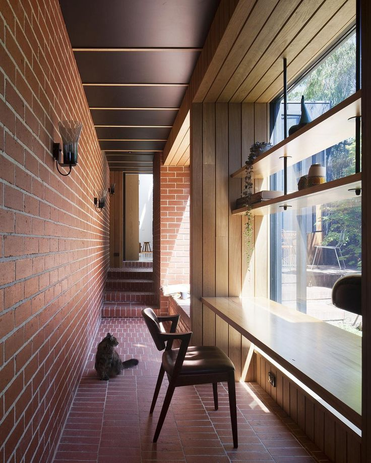 The corridor link in @antmartarch's Carlton Cloister is built entirely from blackbutt cladding and red brick aligning more closely with the external spaces than the interior ones. . Photo by @shannonmcgrath7 #ausdesignreview #architecture #australianarchitecture #australiandesign #design #melbourne #brick #design #interiordesign #home #timber #garden #renovation #cat #window
