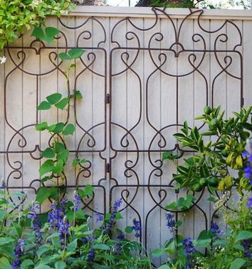 Ornamental trellis against painted fence or wall. What a great look.