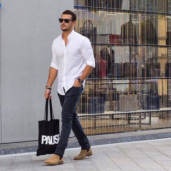 Consider teaming a white long sleeve shirt with charcoal slim jeans to get a laid-back yet stylish look. Camel suede chelsea boots will instantly smarten up even the laziest of looks.   Shop this look on Lookastic: https://lookastic.com/men/looks/long-sleeve-shirt-skinny-jeans-chelsea-boots/18403   — Black Sunglasses  — White Long Sleeve Shirt  — Dark Brown Leather Watch  — Dark Brown Bracelet  — Charcoal Skinny Jeans  — Tan Suede Chelsea Boots  — Black and White Print Canvas Tote Bag