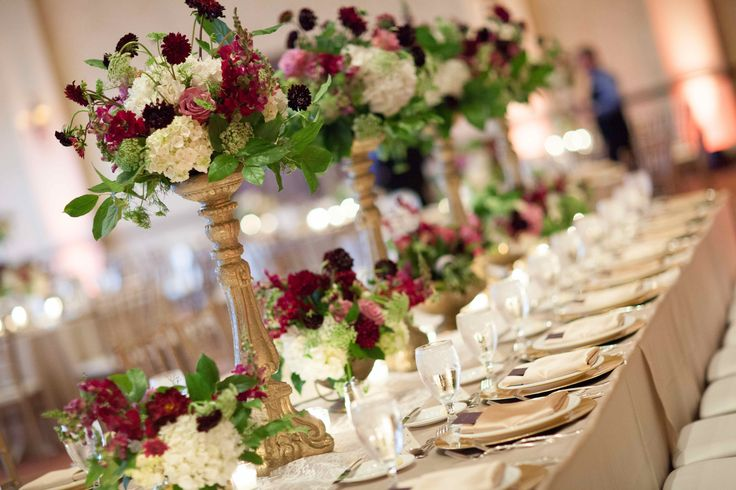 gorgeous and lush king table for the wedding party was filled with tall vintage gold pedestals and low vintage brass vessels filled with burgundy, purple, lavender and white flowers.