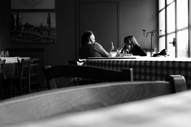 """Ultimi, in una sala ormai vuota e sparecchiata dal caos di voci e posate. Gente informale, magari di passaggio, che si concede un momento in più. """"Forestieri"""" si sarebbe detto una volta. Di loro rimane solo un' immagine… e il sorriso soddisfatto quando salutano e s'incamminano lungo il vialetto d'uscita. © Photo&Testi Maurizio Tosto per Osteria del Dosso."""