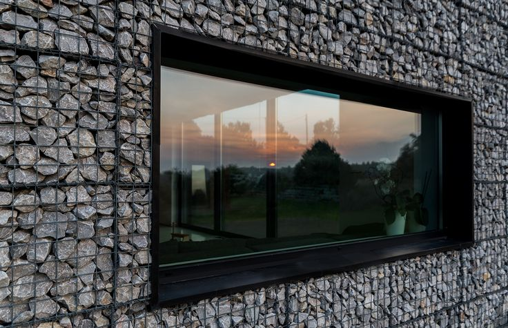 Residência na Paisagem / Kropka Studio -  a principal parte do edifício foi finalizada com gabiões (preenchidos com pedra local) utilizados como revestimento exterior -  um tipo de camuflagem para inserir a residência na paisagem.