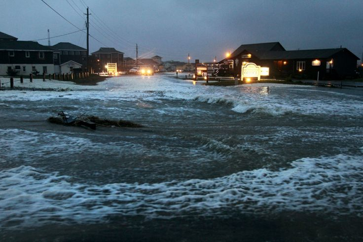Ocean water rolls over state highway NC 12 in Buxton, N.C., on Hatteras Island at dawn on Sunday, Oct. 28, 2012, as Hurricane Sandy works its way north, battering the U.S. East Coast. (AP Photo/The Virginian-Pilot, Steve Earley)